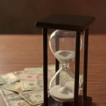 Black hourglass with white sand and money on wooden table